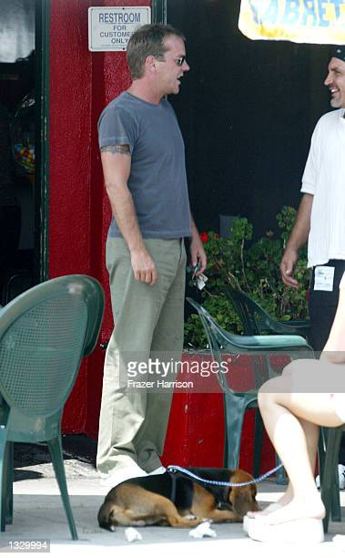 Actor Kiefer Sutherland talks with an unidentified friend after eating at Albano's Brooklyn Pizzeria on August 3 2002 in Los Angeles California