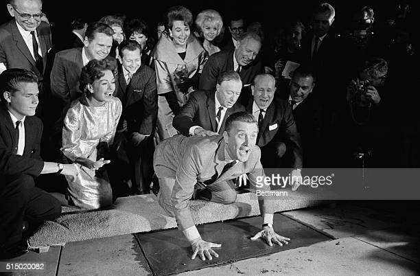 Actor Kirk Douglas , in obvious high spirits, puts his hands in the cement in front of Grauman's Chinese Theater November 1st. At right, bandleader...