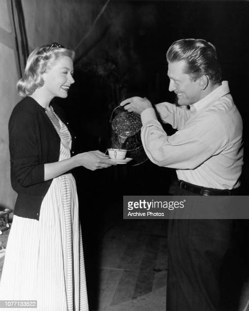 Actor Kirk Douglas pours coffee for his costar Gloria Grahame on the set of the film 'The Bad and the Beautiful' 1952