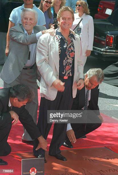 Actor Kirk Douglas pushes his son actor Michael Douglas down in the cement at the Chinese Theater during the hand/footprint ceremony September 10...