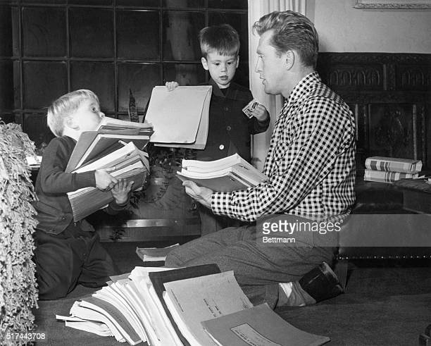 Actor Kirk Douglas sorts through scripts with his young sons Michael and Joel
