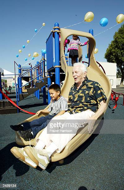Actor Kirk officially opens the Florence Avenue School playground by taking pupil Jose Aguilar aged 5 down the new equipment on September 3 2003 in...