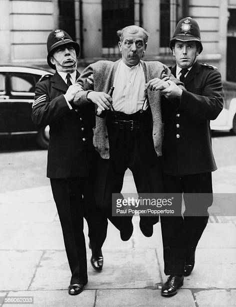 Actor Larry Noble is lead away by actors Leo Franklyn and Brian Rix dressed as policeman during rehearsals for the comedy play 'A Policeman's Lot'...