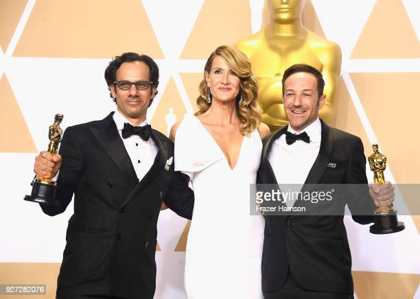 Actor Laura Dern poses with producers Dan Cogan and director Bryan Fogel winners of the Best Documentary Feature award for 'Icarus' in the press room...