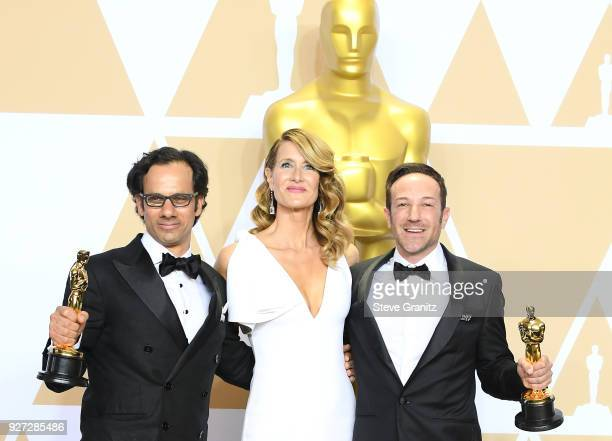 "Actor Laura Dern with producer Dan Cogan and director Bryan Fogel winners of the Best Documentary Feature for ""Icarus"" pose in the press room during..."