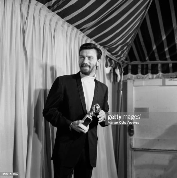 Actor Laurence Harvey poses with his Golden Globe he won for World Film Favorite in Los Angeles California
