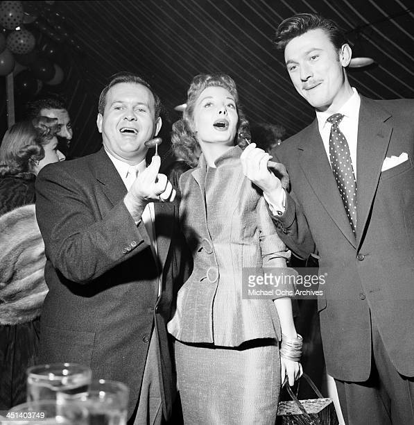 Actor Laurence Harvey with Johnny Grant and Norma Brooks attend a Mike Todd party in Los Angeles, California.