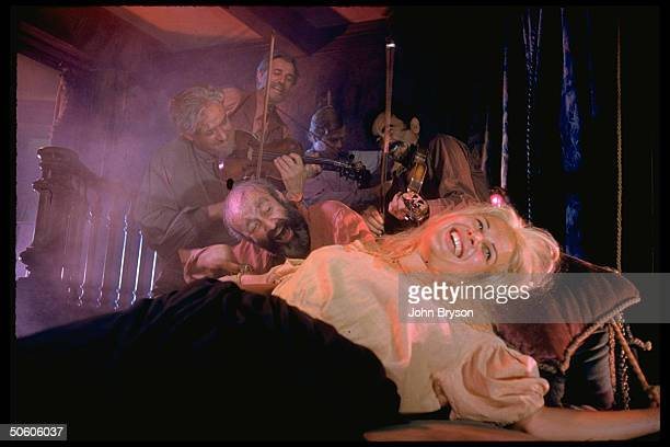 Actor Lee J Cobb laughing as he tickles woman tied to bed musicians play in scene fr film The Brothers Karamazov based on novel by Dostoevsky