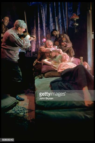 Actor Lee J Cobb pouring alcohol on head of woman tied to bed as musicians play in scene fr film The Brothers Karamazov based on novel by Dostoevsky