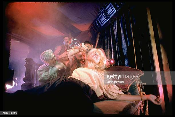 Actor Lee J Cobb pouring alcohol on woman tied to bed as musicians play in scene fr film The Brothers Karamazov based on novel by Dostoevsky