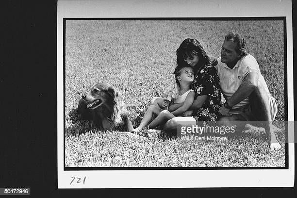 Actor Lee Majors w his 3rd wife Karen daughter Nikki relaxing on lawn w their golden retriever dog at home