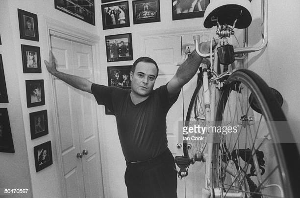 Actor Leonard Whiting posing next to bicycle hanging on wall rack in foyer of his Victorian row house in Camden Town