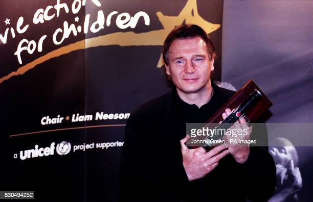 Actor Liam Neeson holding the Star Wars lightsabre that he donated as he spearheaded a huge fund raising auction as a weapon in the fight to stop the...