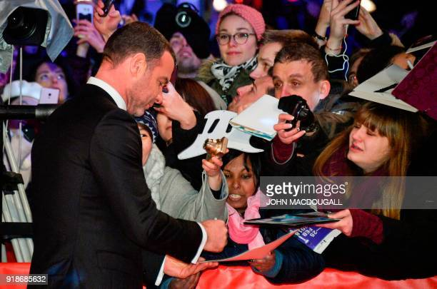 US actor Liev Schreiber signs autographs as he arrives on the red carpet for the opening ceremony of the 68th Berlinale film festival with the...