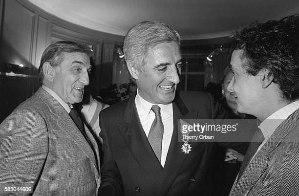 Actor Lino Ventura and singer Michel Sardou congratulate screenwriter Jean-Loup Dabadie on his Legion d'Honneur award. Comedian Raymond Devos...