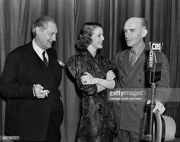Actor Lionel Barrymore and actress Loretta Young stand with actor James Gleason at the microphone at CBS radio in Los Angeles California