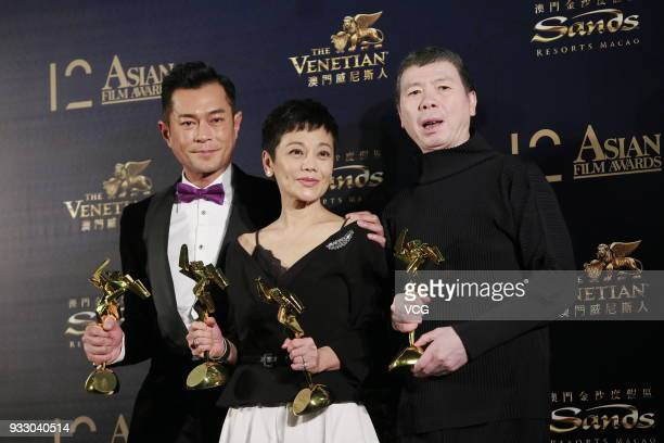 Actor Louis Koo actress Sylvia Chang and director Feng Xiaogang pose with trophies at backstage during the 12th Asian Film Awards at the Venetian...