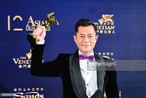 Actor Louis Koo poses with trophy backstage during the 12th Asian Film Awards at the Venetian Hotel on March 17 2018 in Macao China