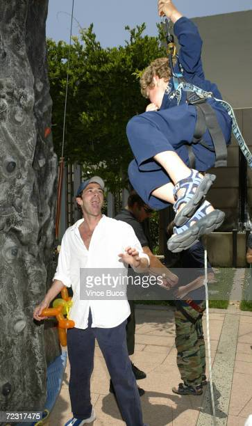 Actor Luke Perry reacts to son Jack's climbing ability at an afterparty for the premiere of Garfield The Movie at the Twentieth Century Fox studio...