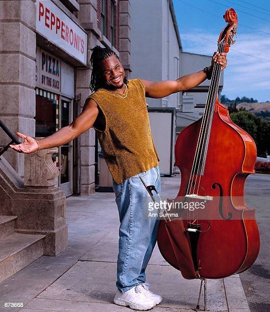"""Actor Malcolm-Jamal Warner poses with his bass July 9, 1999 in Sherman Oaks, CA. Warner starred in """"The Cosby Show"""" as Bill Cosby's son Theodore..."""