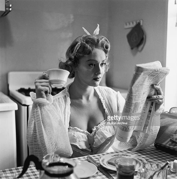 Actor Marion Brash sits at the breakfast table reading a newspaper and holding a cup of coffee She wears a bathrobe and a nightgown There is a piece...