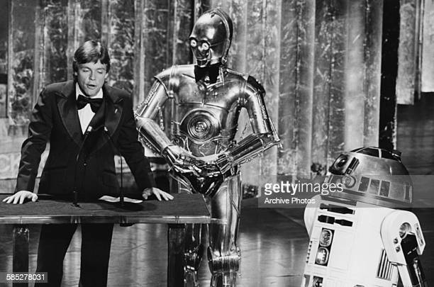 Actor Mark Hamill presenting an award with his Star Wars costars C3PO and R2D2 at the 50th Academy Awards Los Angeles April 3rd 1978
