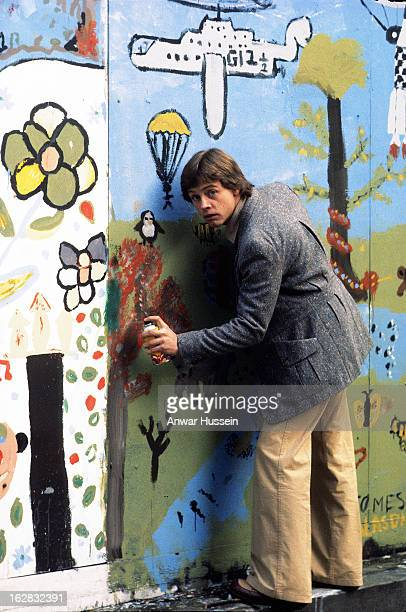 Actor Mark Hamill who plays Luke Skywalker in Star Wars paints graffiti on a wall during a visit to London on January 11979 in London England