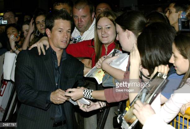 """Actor Mark Wahlberg acknowledges fans at the UK charity premiere of """"The Italian Job"""" at the Empire Leicester Square September 15, 2003 in London,..."""