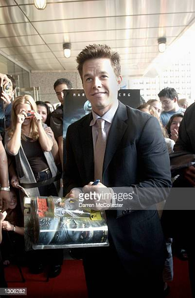 Actor Mark Wahlberg autographs a box with an action figure made in his likeness July 26 2001 in Boston Massachusetts at the opening of his new film...