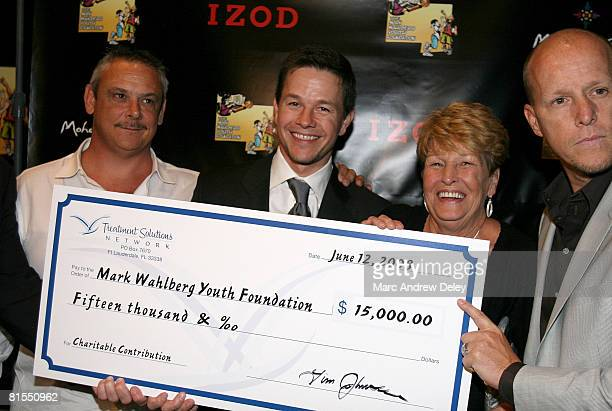 Actor Mark Wahlberg his mother Alma Wahlberg and brother Jim Wahlberg are presented with $15000 during the M Night Shyamalan's 'The Happening' After...