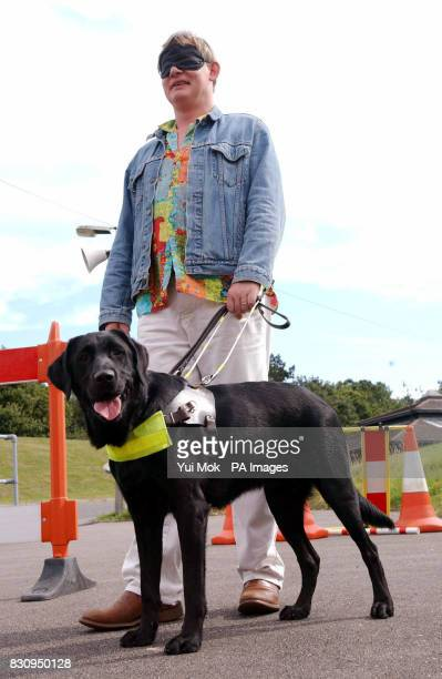 Actor Martin Clunes is led around an obstacle course by Buster the guide dog a labradorcross retriever aged 18 months at The Guide Dogs for the Blind...