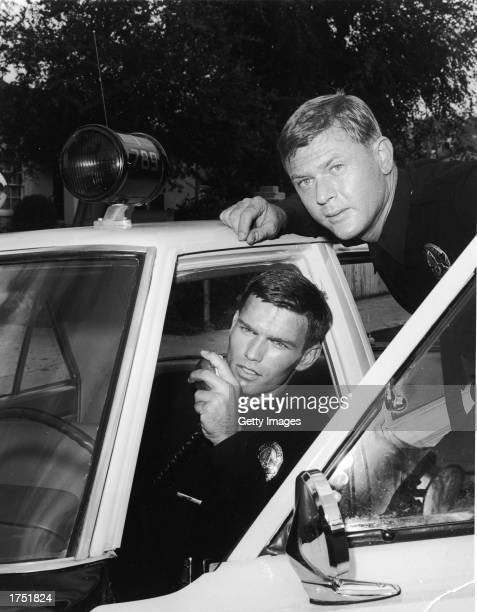 Actor Martin Milner leans over the door of a patrol car as Kent McCord talks on the police radio in a promotional still for the television series...