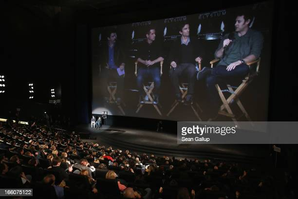 Actor Matt Damon and host Steven Gaetjen attend the trailer launch event for Elysium as producer Simon Kinberg actor Sharlto Copley and director...