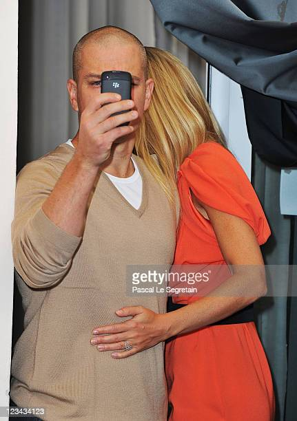 Actor Matt Damon takes a photo of the press as actress Gwyneth Paltrow walks by at the Contagion photocall during the 68th Venice Film Festival at...