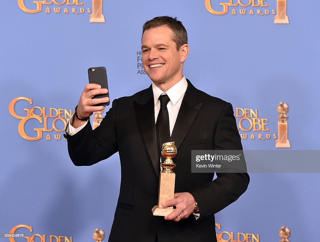 Actor Matt Damon, winner of Best Performance in a Motion Picture - Musical or Comedy for 'The Martian,' takes a selfie in the press room during the 73rd Annual Golden Globe Awards held at the Beverly Hilton Hotel on January 10, 2016 in Beverly Hills, California.