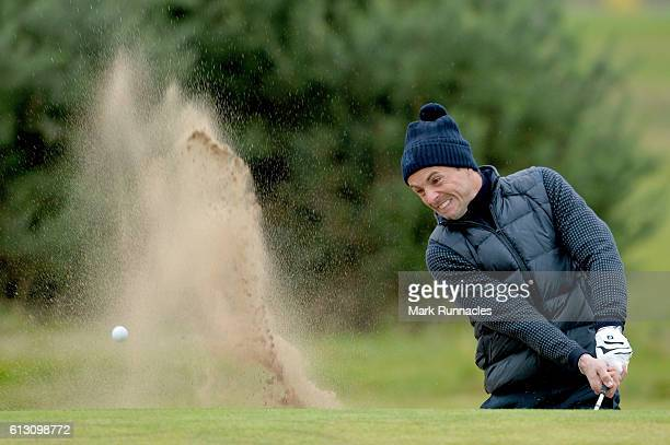 Actor Matthew Goode plays out from the bunker on the 11th hole during the second round of the Alfred Dunhill Links Championship on the Championship...