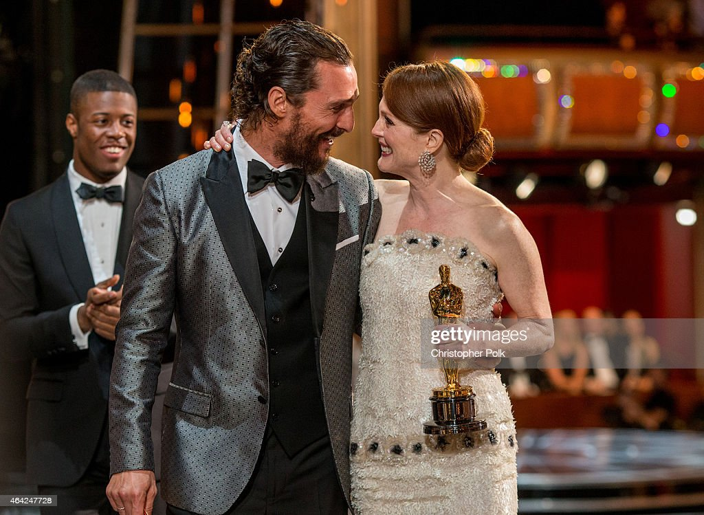 Actor Matthew McConaughey escorts winner Julianne Moore offstage as she holds her statuette for Actress in a Leading Role during the 87th Annual Academy Awards at Dolby Theatre on February 22, 2015 in Hollywood, California.