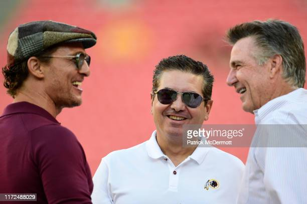 Actor Matthew McConaughey talks with Washington Redskins owner Dan Snyder and Redskins team president Bruce Allen before a preseason game between the...