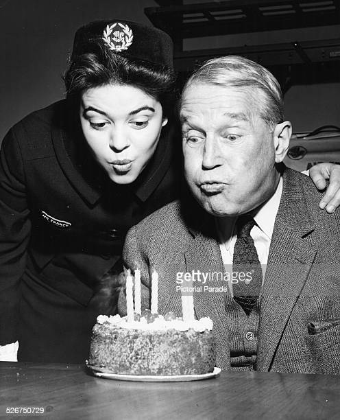 Actor Maurice Chevalier blowing out the candles on his birthday cake helped by an air stewardess as he arrives with Air France at New York...