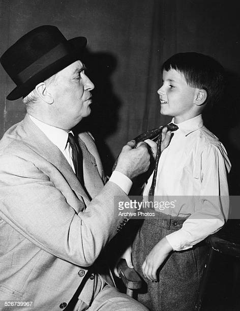 Actor Maurice Chevalier helping young Martin Stevens with his tie on the set of the movie 'Count Your Blessings' circa 1958