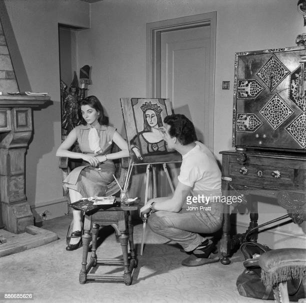 Actor Maxwell Reed paints a portrait of his wife actress Joan Collins wearing a crown at their flat in Hanover Square London 8th May 1953