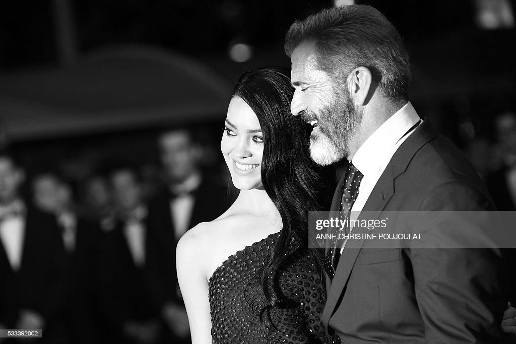 US actor Mel Gibson (R) and his partner Rosalind Ross pose as they arrive on May 21, 2016 for the screening of the film 'Blood Father' at the 69th Cannes Film Festival in Cannes, southern France. / AFP / ANNE