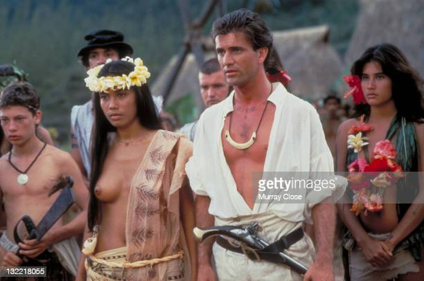 Actor Mel Gibson as mutineer Fletcher Christian and Tevaite Vernette as Mauatua in the film 'The Bounty', 1984. English actor Dexter Fletcher is on...