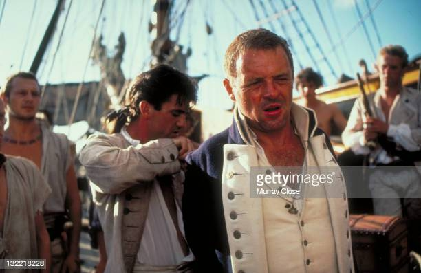 Actor Mel Gibson as mutineer Fletcher Christian and Welsh actor Anthony Hopkins as Captain Bligh in the film 'The Bounty' 1984 In the background are...