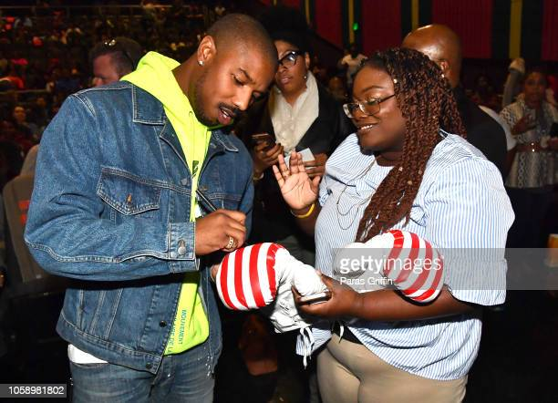 Actor Michael B Jordan autographs boxing gloves of a moviegoer during the Creed 2 Atlanta screening at Regal Atlantic Station on November 7 2018 in...