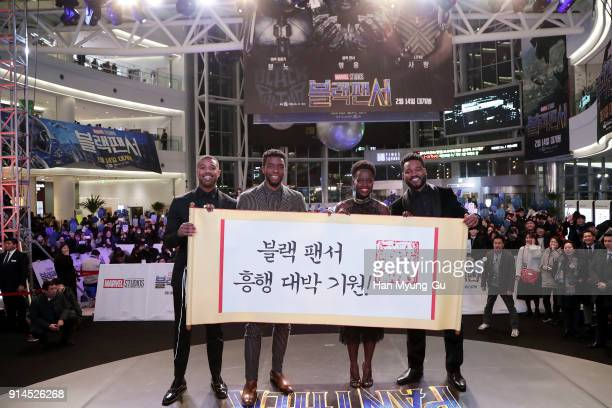 Actor Michael B Jordan Lupita Nyong'o Chadwick Boseman and director Ryan Coogler hold placard wishing the success of the movie in the red carpet...