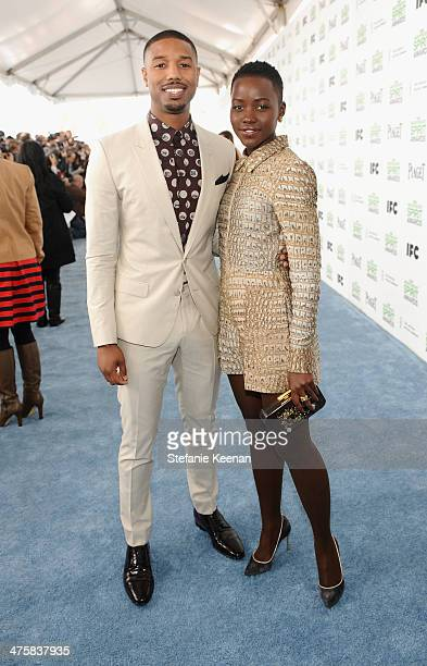 Actor Michael B Jordan wearing Piaget and actress Lupita Nyong'o attend the 2014 Film Independent Spirit Awards at Santa Monica Beach on March 1 2014...