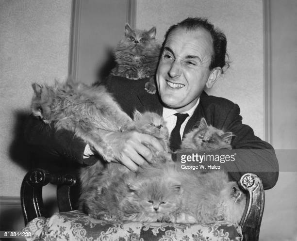 Actor Michael Barrington star of the revue 'Salad Days' with an armful of cats at the home of their owner Miss Irene Stutman of Cricklewood London...