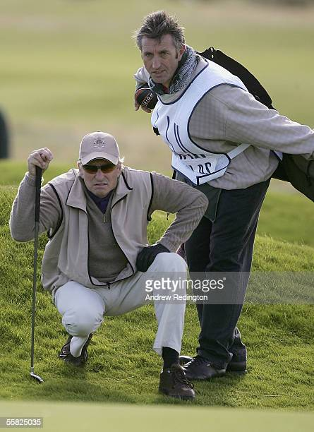 Actor Michael Douglas gets some advice from his caddie before playing his shot to the 16th green during the first round of the Dunhill Links...