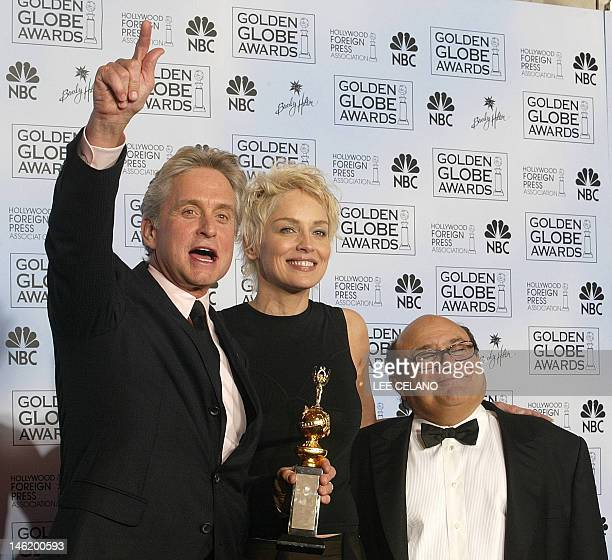 Actor Michael Douglas holds his Cecil B DeMille award with presenters Sharon Stone and Danny Devito at the 61st Golden Globe awards in Beverly Hills...